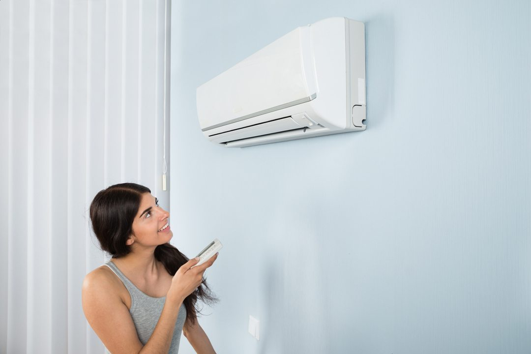 Young Woman Operating Air Conditioner With Remote Controller