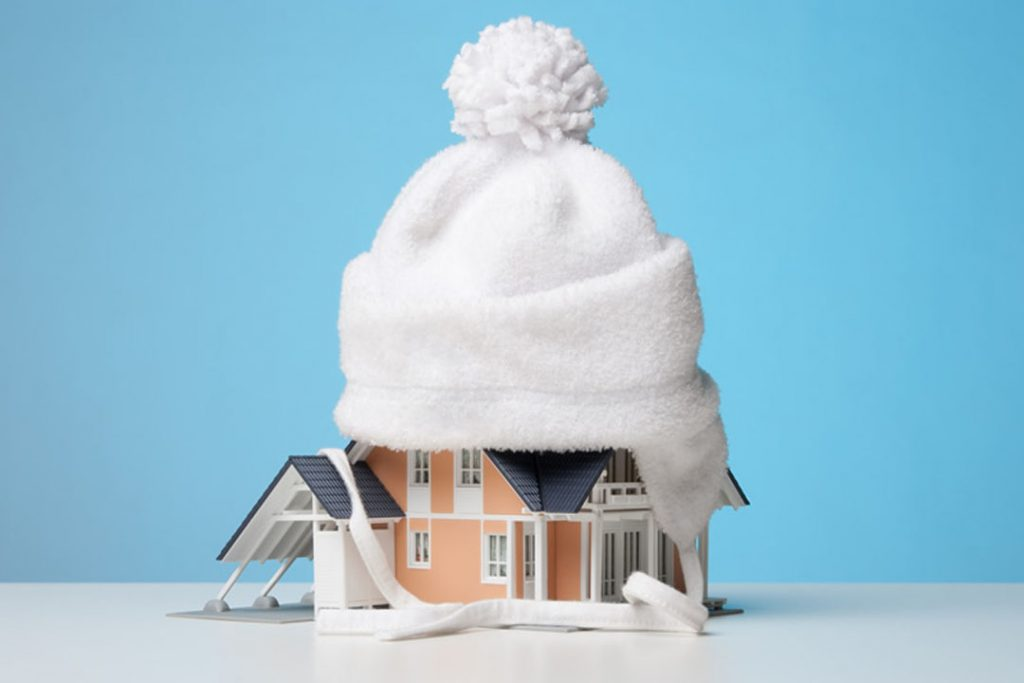 High resolution image of a miniature toy house fitted with a winter cap on top, on a plain white surface.