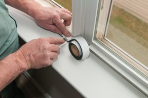 A man applying white sealing tape to a window frame