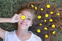 Girl lying in field with yellow flowers