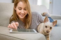 Girl with dog using a a tablet